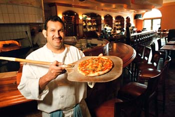 Seafood and More: Eladio Chavez cooks up a pizza in the brand-new wood-fired oven at Steamer's. Photo by George Sakkestad